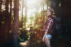 Female backpacker set out on forest trail Royalty Free Stock Photos