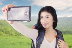 Female backpacker taking picture at hill Royalty Free Stock Photography