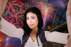Female backpacker taking selfie in fireworks party Stock Photo