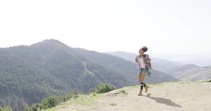 Female backpacker walking on top of mountain stock footage