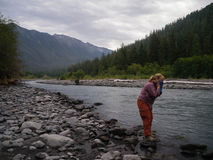 Female Backpacker Washing Up at a River Royalty Free Stock Photo