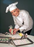 Female Baker. Standing in bakery piping flower decorations Royalty Free Stock Images
