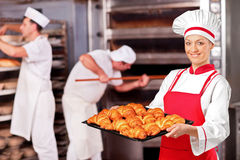 Female baker in bakery. A female baker holding freshly baked croissants in bakery Stock Image