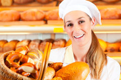 Female baker in bakery selling bread by basket. Female baker or saleswoman in her bakery selling fresh bread, pastries and bakery products in basket Royalty Free Stock Photography
