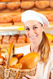 Female baker in bakery selling bread by basket. Female baker or saleswoman in her bakery selling fresh bread, pastries and bakery products in basket Stock Photography