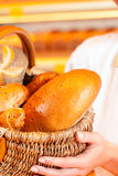 Female baker in bakery selling bread by basket Royalty Free Stock Images