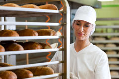 Female baker baking bread. Female baker baking fresh bread in the bakehouse Stock Photos