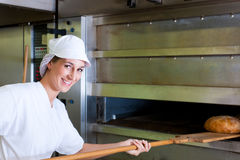 Female baker baking bread Royalty Free Stock Images