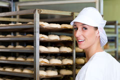 Female baker baking bread rolls Stock Photos