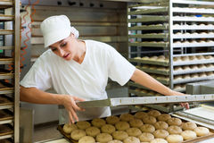 Female baker baking bread rolls. Female baker baking fresh bread rolls in the bakehouse Royalty Free Stock Photography