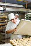 Female baker baking bread rolls. Female baker baking fresh bread rolls in the bakehouse Stock Photography