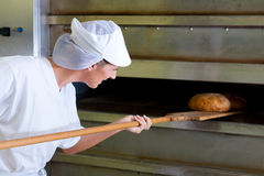 Female baker baking fresh bread in the bakehouse. Female baker baking bread fresh Stock Photos