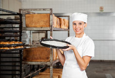 Female Baker Carrying Dough Tray At Bakery Stock Photography
