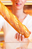 Female baker in her bakery with baguette Royalty Free Stock Photography