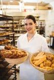 Female baker holding basket of sweet foods. At bakery shop Stock Photo