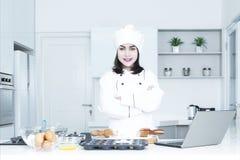 Female baker looks confident in kitchen Stock Image