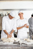 Female Baker Making Dough Balls By Male Colleague. Portrait of young female baker making dough balls by male colleague in bakery stock image