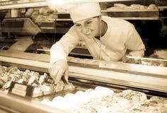 Female baker offering fresh pastry Royalty Free Stock Image