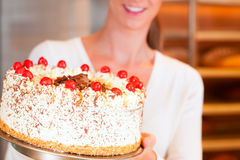 Female baker or pastry chef with torte Royalty Free Stock Images