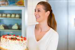 Female baker or pastry chef with torte Stock Images