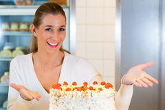 Female baker or pastry chef with torte Royalty Free Stock Photo