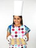 Female baker with a plate of cookies. Smiling royalty free stock photography