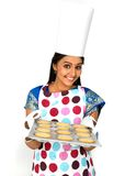 Female baker with a plate of cookies. And smiling Stock Images