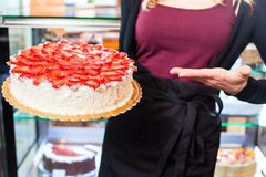 Female baker presenting cake in confectionery Royalty Free Stock Photo