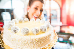 Female baker presenting cake in confectionery Royalty Free Stock Images