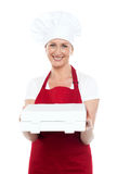 Female baker presenting pizza to you in a box Stock Photography