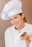 Female baker presenting you with eclair. Female baker presenting you with an eclair stock image