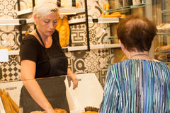 Female baker or saleswoman in her bakery with female customer Stock Image
