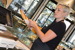 Female baker or saleswoman in her bakery selling fresh bread Royalty Free Stock Photo