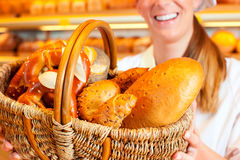 Female baker selling bread by basket in bakery Royalty Free Stock Images