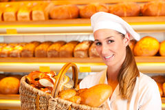 Female baker selling bread by basket in bakery. Female baker or saleswoman in her bakery selling fresh bread, pastries and bakery products in basket Stock Images