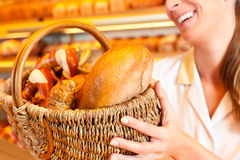 Female baker selling bread by basket in bakery. Female baker or saleswoman in her bakery selling fresh bread, pastries and bakery products in basket Royalty Free Stock Image