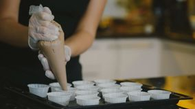 Female baker squeezes batter into molds in kitchen indoor. stock footage