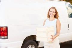 Female Baker Unloading Cakes From Van Stock Image