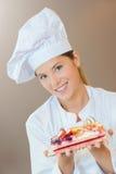 Female bakery chef with fruit cake Stock Image