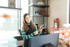 Female Bakery Owner Inserting Credit Card In POS Terminal. Portrait of content salesgirl holding credit card and reader in bakery royalty free stock image