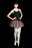 Female Ballerina. A young asian ballerina standing on tip toe against black background stock photography
