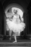 Female ballerina posing. Can you be more graceful Monochrome shot of an elegant female ballet dancer posing in an archway soft focus royalty free stock image