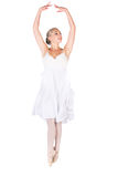 Female ballet dancer. Beautiful female ballet dancer isolated on a white background. Ballerina is wearing a white feathered dress and pointe shoes Stock Photo