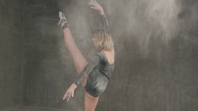 Female ballet dancer in black body suit perform on stage in theater and using white powder or white smoke dust. Dancer