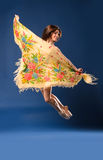 Female ballet dancer jumping with headscarf. Professional female ballet dancer jumping with large headscarf as bird on dark studio background Royalty Free Stock Photography