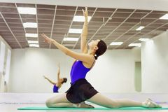 Female ballet dancer in Pointe shoes warming up on the Mat royalty free stock image