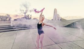 Female ballet dancer practicing dance moves using a smoke bomb. Ballet artist practicing dance moves outdoors using a pink smoke bomb. Female ballet dancer using Royalty Free Stock Photography