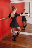 Female Ballet Dancer Practicing In Front Of Mirror. Full length of young female ballet dancer practicing in front of mirror at studio Royalty Free Stock Photography