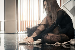 Female ballet dancer puts pointes on. Female ballet dancer sitting on a floor in a dancing class putting on her pointes Stock Photo