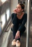 Female ballet dancer sitting against window Royalty Free Stock Photo